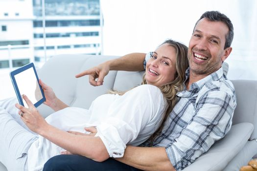 Expecting couple sitting on sofa and using digital tablet