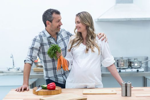 Pregnant woman looking at man while holding carrots
