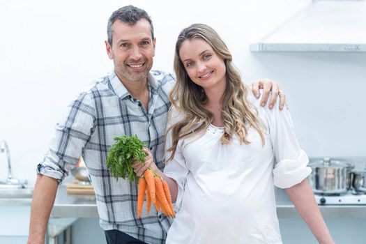 Portrait of pregnant woman looking at camera while holding carrots