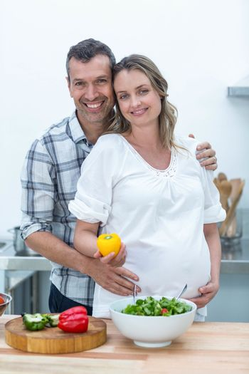 Portrait of pregnant couple looking at camera in kitchen