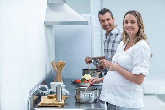 Pregnant couple preparing food in kitchen