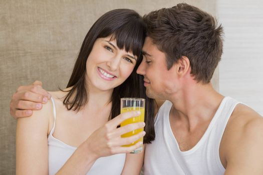 Smiling woman drinking juice while man embracing on bed in bedroom