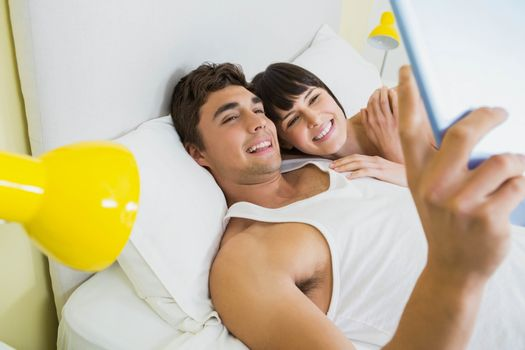 Couple lying on bed using digital tablet in bedroom