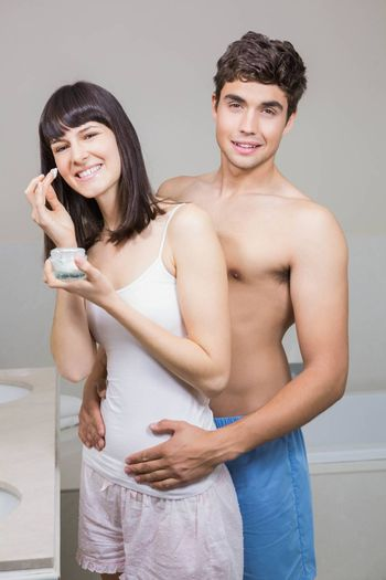 Portrait of young couple smiling and embracing each other in bathroom