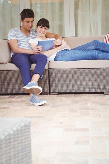 Young couple relaxing on sofa and using digital tablet in living room
