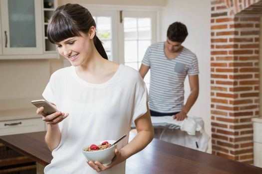 Woman using mobile phone and having breakfast cereals while man ironing a shirt in background