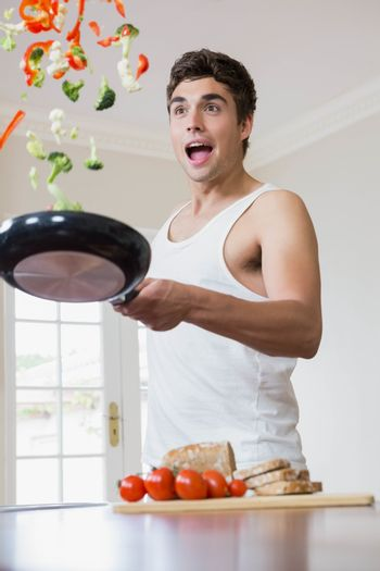 Young man tossing vegetables in frying pan