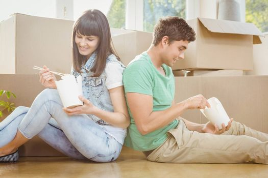 Young couple sitting on the floor and eating noodle in their new house