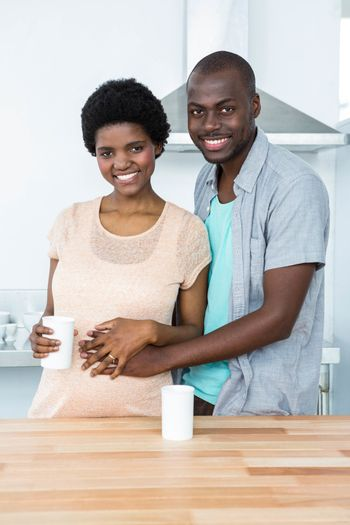 Portrait of pregnant couple embracing each other while having cup of coffee at kitchen