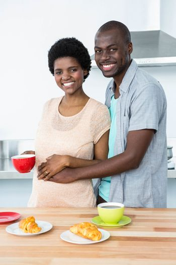 Portrait of smiling pregnant couple having breakfast in kitchen at home