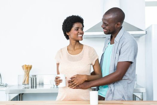 Pregnant couple embracing each other while having cup of coffee at kitchen