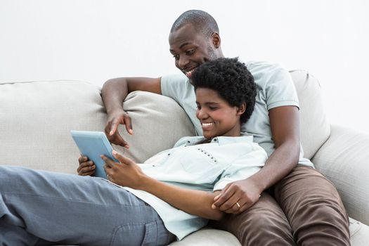 Pregnant couple using digital tablet on sofa in living room