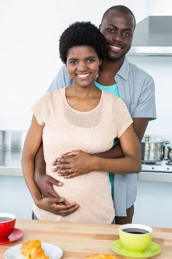 Portrait of pregnant couple embracing each other while having breakfast at kitchen