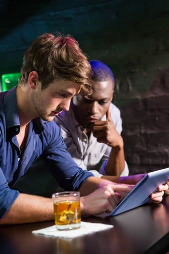Two men having whiskey and using digital tablet at bar counter in bar