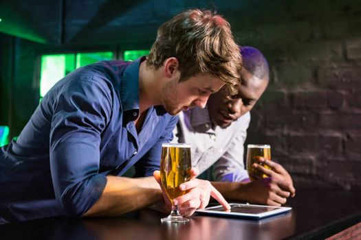 Two men using digital table while having beer at bar counter in bar