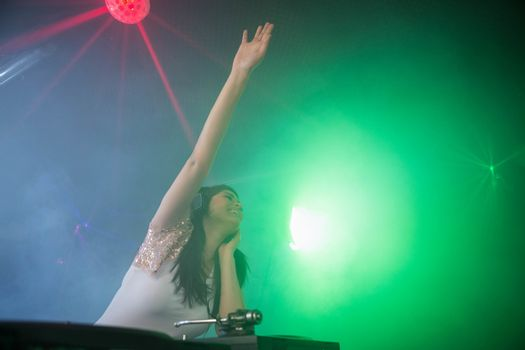 Pretty female DJ waving her hand while playing music at nightclub
