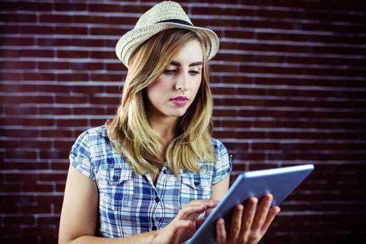 Pretty blonde woman using tablet on brick wall background