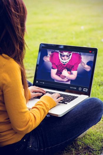 Woman using laptop in park against composite image of american football players