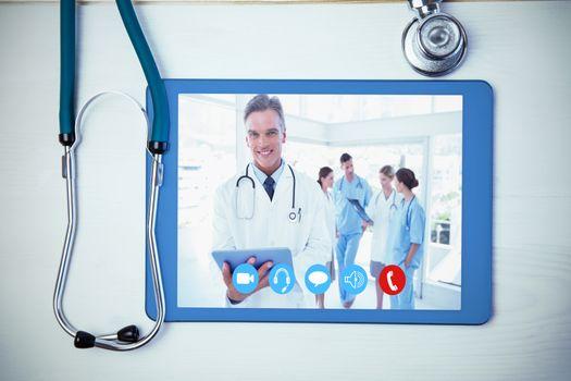 Smiling doctor holding digital tablet against tablet and stethoscope on desk