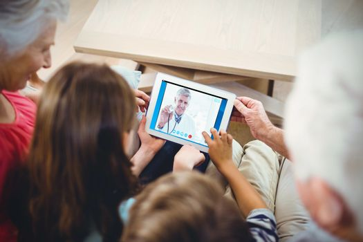Happy doctor smiling at camera and showing his stethoscope  against family using tablet