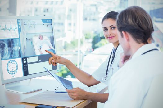 Composite image of doctor showing the screen of a computer to a colleague