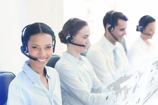 Composite image of business people with headsets using computers
