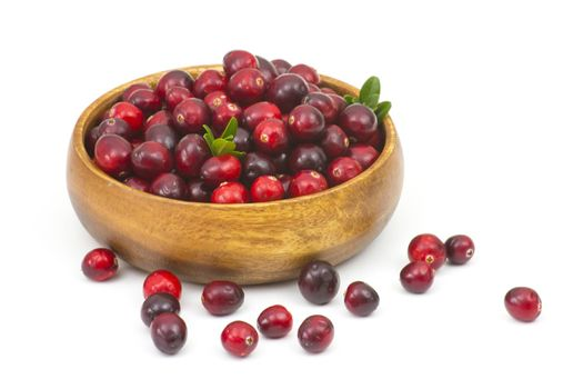 Cranberries in wooden bowl on white background.