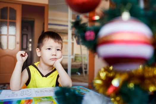 Dreamy little boy sitting on a background Christmas tree writes his wish list on a piece of paper and dreaming about gifts from Santa Claus. He is preparing for the Christmas and New Year holidays.