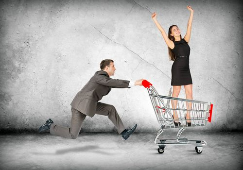 Businessman pushing shopping cart with business lady on grey background