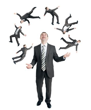Businessman juggling little people isolated on white background