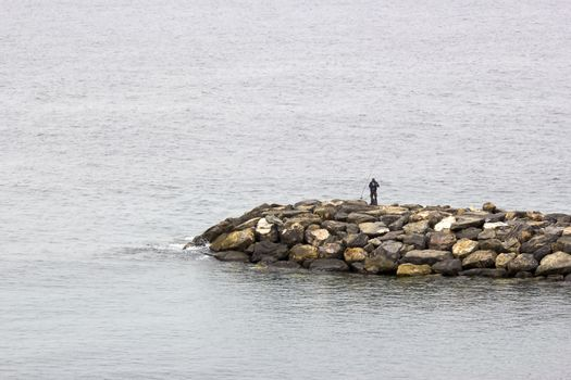 Fisher man with fishing rod on the stone groyne
