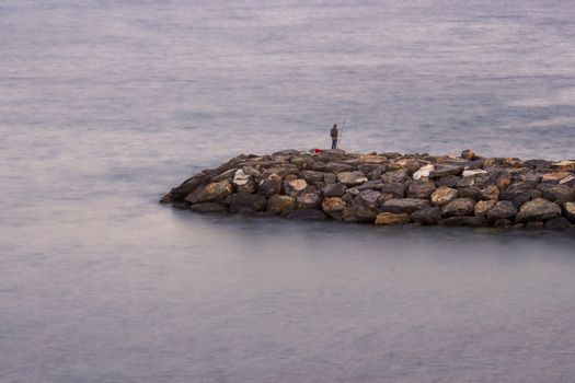 Fisher man with fishing rod on the stone groyne at sunset