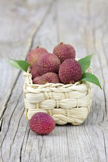 fresh lychees in a basket on wooden background