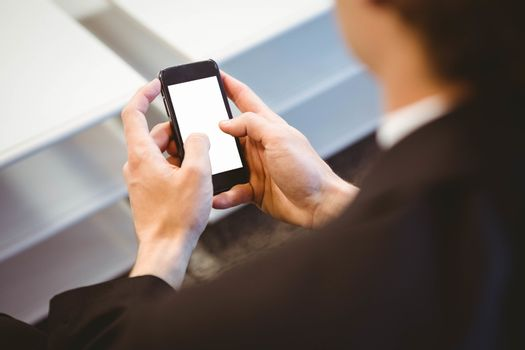 Businessman text messaging on smartphone
