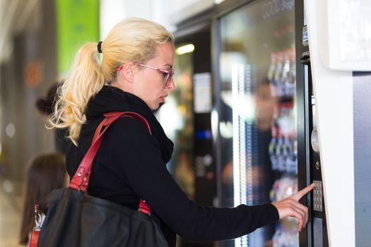 Lady using  a modern vending machine