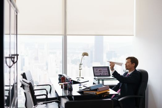 Bored Business Man Throwing Paper Airplane In Office