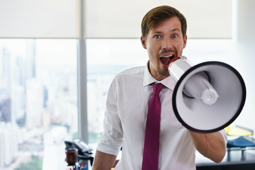 Young executive office worker holding megaphone and speaking at camera with confidence and funny expression. Copy space