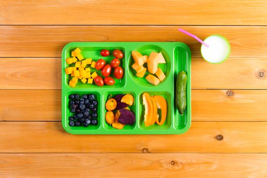 Single green lunch tray of fruit