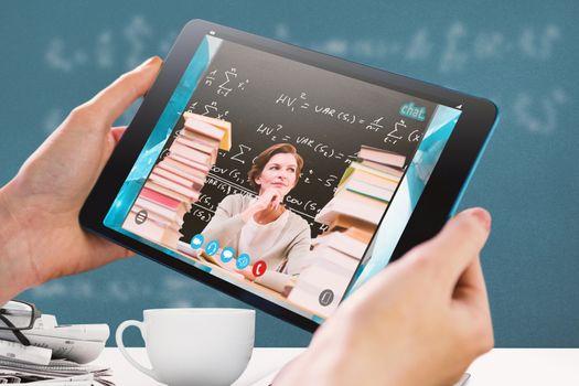 Hands holding tablet against blackboard