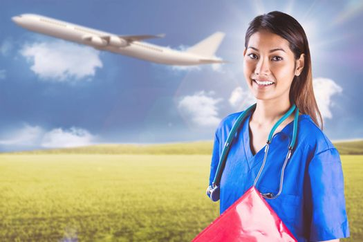 Asian nurse with stethoscope looking at the camera against sunny green landscape