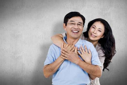 Smiling couple holding each other against white and grey background