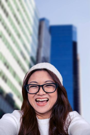 Asian woman smiling at the camera against skyscraper