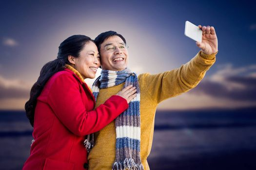 Older asian couple on balcony taking selfie against scenic view of sea against sky