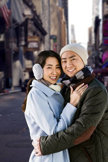 Portrait of couple embracing against picture of a city