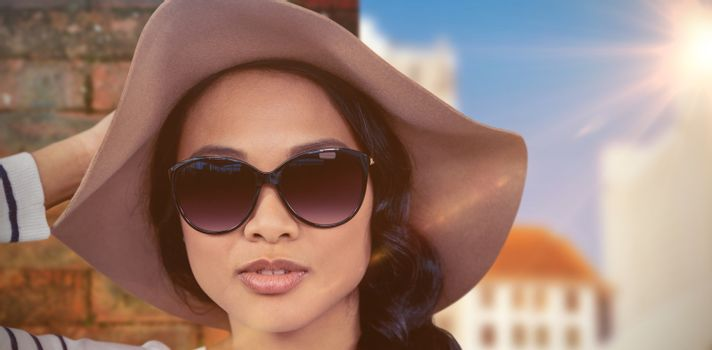Attractive Asian woman with hat and sunglasses against view of brick wall
