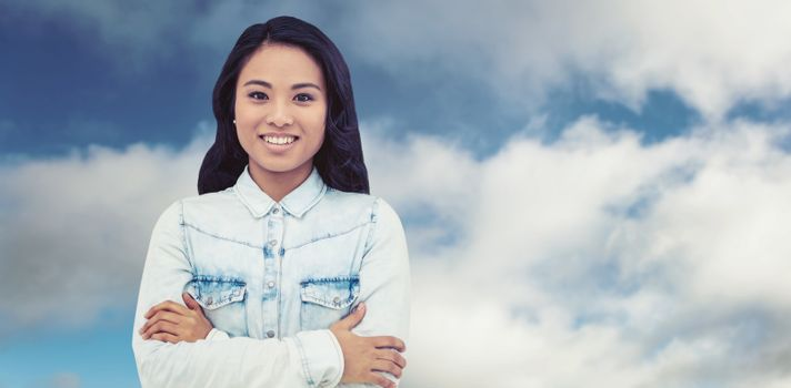 Asian woman with arms crossed smiling against blue sky with clouds