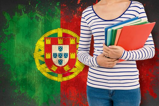 Mid section of woman holding files against portugal flag in grunge effect