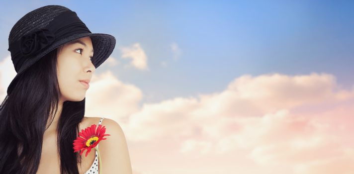 Cheerful woman with flower looking away wearing a hat against beautiful blue cloudy sky