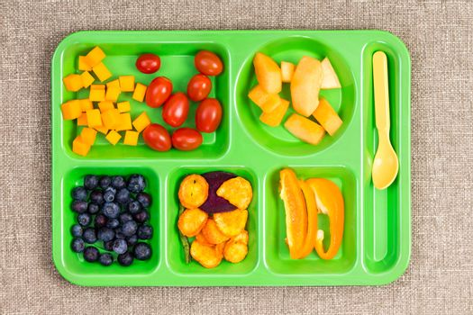 Small plastic lunch tray with fruit and spoon