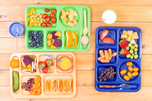 Three colorful lunch trays on table
